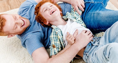 photo of dad and boy playing on the carpet